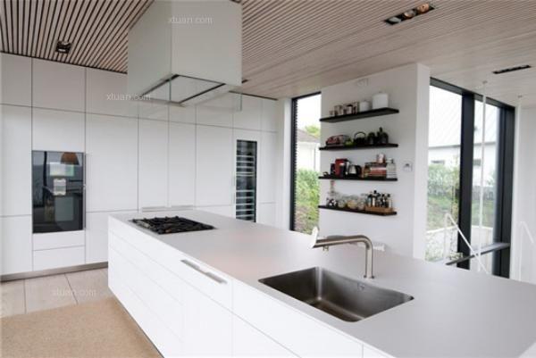 隔断,使厨房成为一个独立的平台,但开放式的设计使二厅空间双向拓宽,在视觉上显得更加宽敞。整体橱柜集烹饪和收纳于一体,大大节省了厨房空间。吧台除了用于食物摆放,也成为了简易的用餐区和收纳空间,物尽其用。    厨房装修效果图四   长方形的白色厨房台面,使得开放式厨房气派大方,同时它具有多个储物柜,有着强大的收纳作用。宽大的台面也可以摆放多种食材,在主人招待客人来到海边举办篝火晚会等活动时,它将派上大用场。    厨房装修效果图五   设计师采用通透玄关扩展空间,巧妙的解决了这个不大的空间给人带来的压抑感